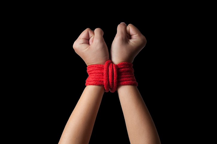 Hands of a missing kidnapped, abused, hostage, victim woman tied up with rope in emotional stress and pain, afraid, restricted, trapped, call for help, struggle, terrified.