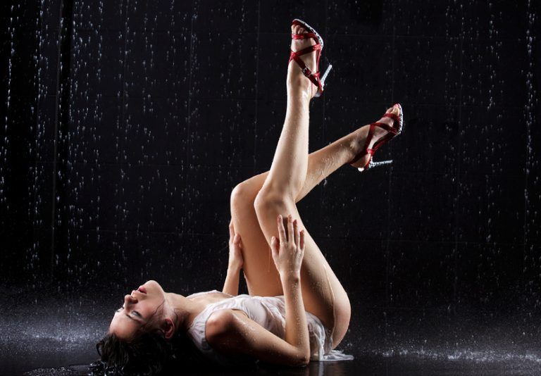 Young sexy woman lying on the floor of a shower, getting ready to enjoy some shower sex