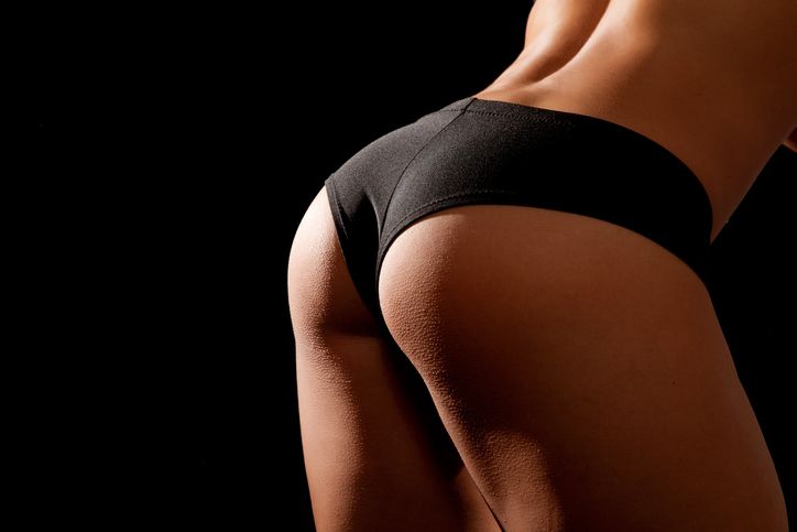 Young tanned woman with beautiful sporty buttocks wearing black sexy sporty style shorts