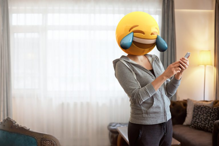 Woman wearing emoji masks while looking at her phone.