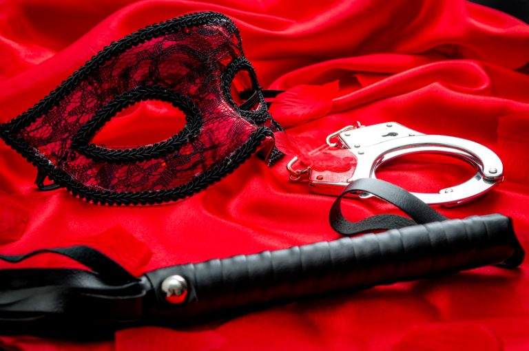 BDSM concept: flogger (whip), handcuffs and eyemask on red satin