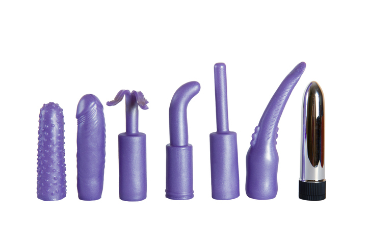 Purple sex toys for woman - vibrator and caps isolated on a white background