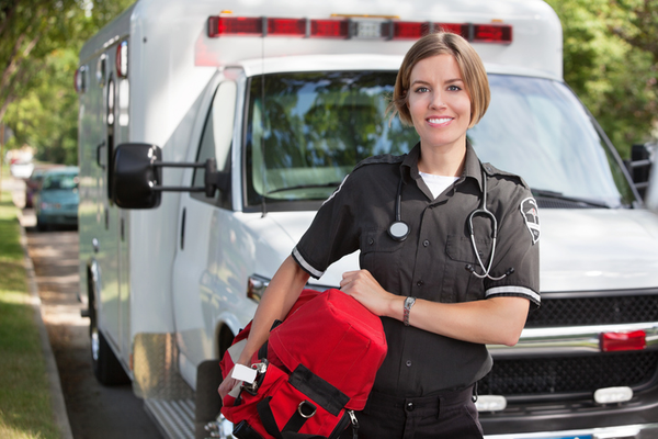 A woman stands in front of an ambulance