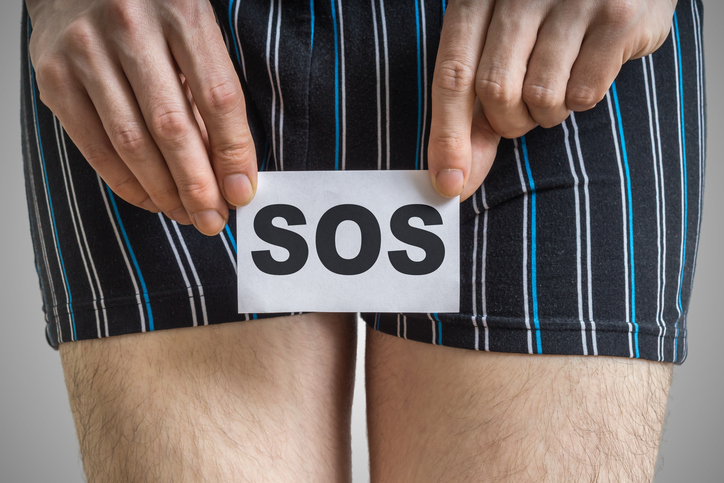 Urinary or prostate problems concept. Young man holds paper with SOS above crotch.
