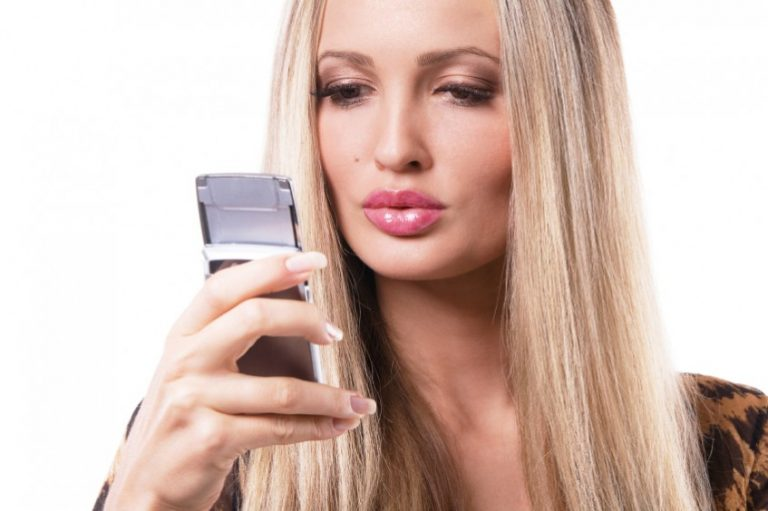 Blonde woman sending message on phone