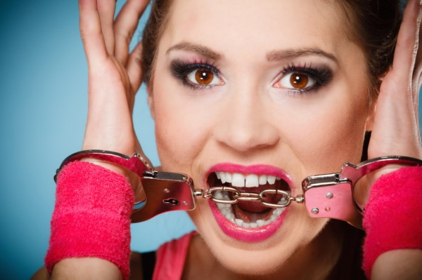 woman in pink handcuffs biting the link between