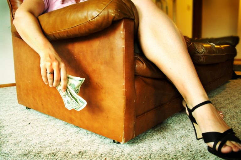 A sex worker sitting in a chair and holding money