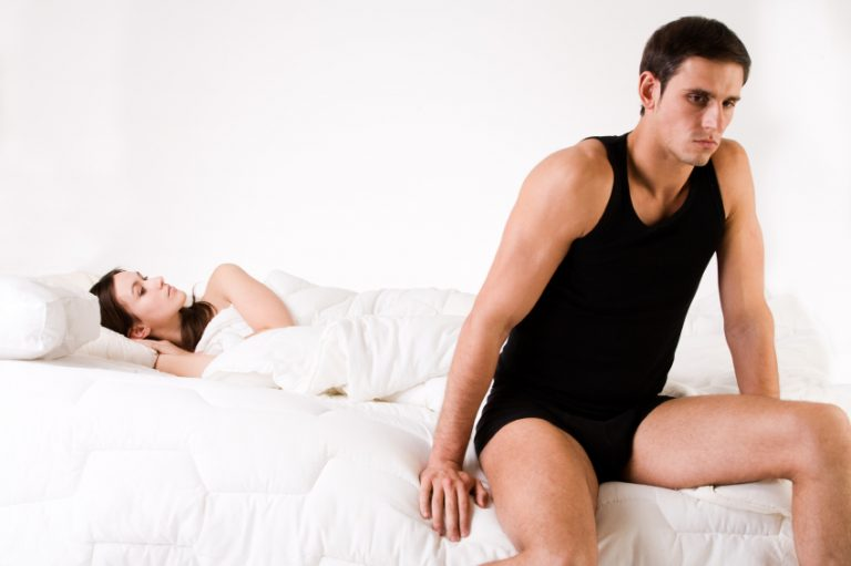 A man sitting on a bed while his partner sleeps. He has sex worries on his mind