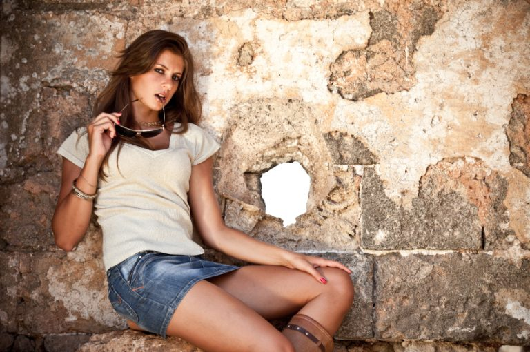 Sexy woman in skirt against a wall