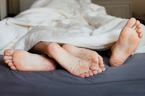 Lovers' feet in the bed