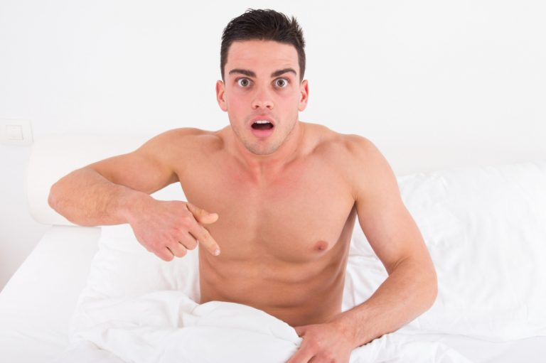 surprised and shocked half naked young man in bed looking down at his underwear at his penis under white covers sheet in badroom. Concept photo of male sexuality and man sex problems, domestic atmosphere.