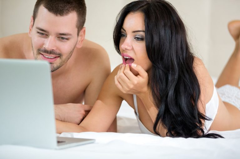 A sexy couple lie down in bed. They watch porn together