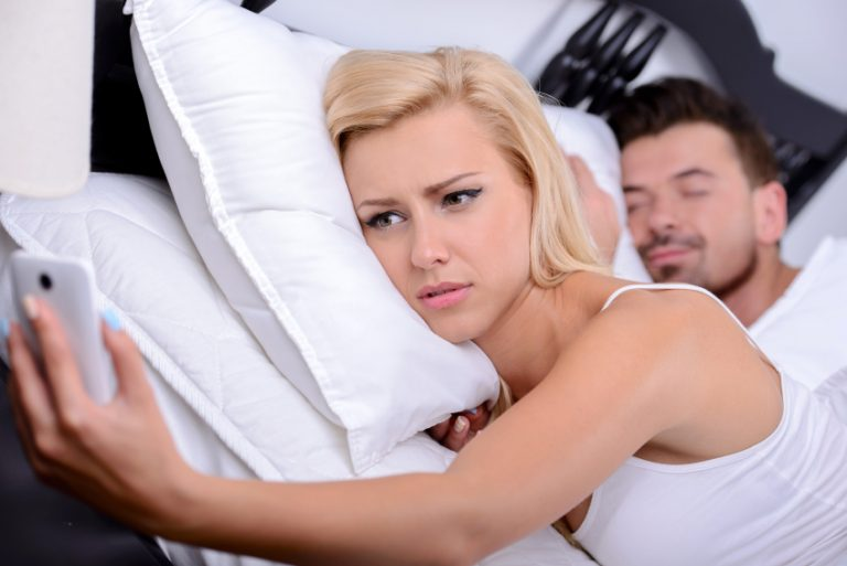 Woman looks at phone while husband sleeps in bed