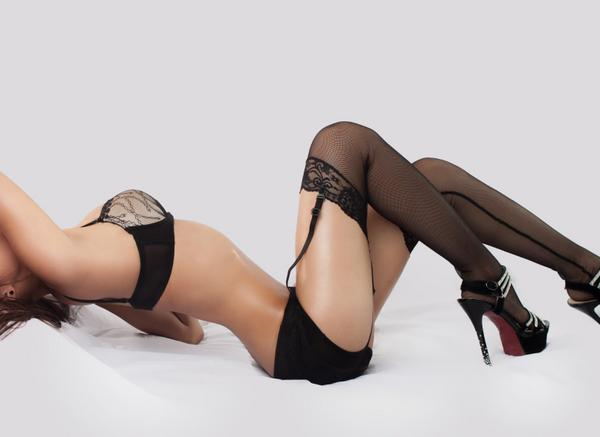 A woman lying back in her lingerie, doing a kegel exercise