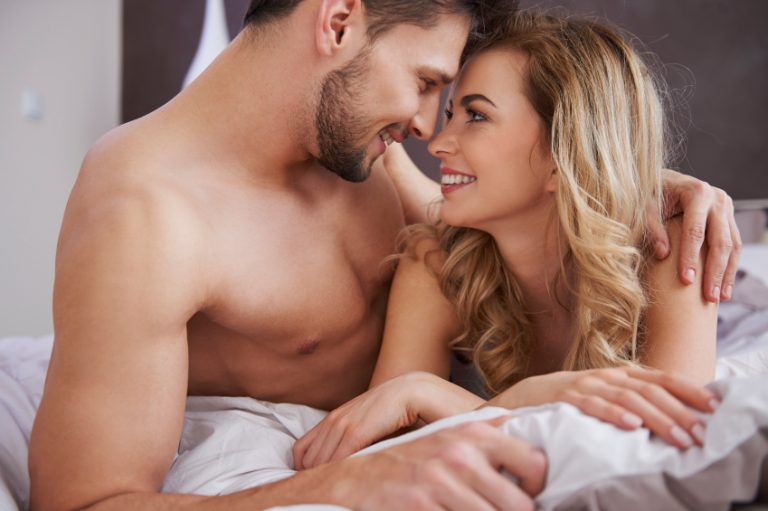 A couple in bed enjoying the many sex benefits