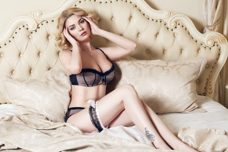 Beautiful sexy long-haired blonde woman sitting on a bed with pillows in lace lingerie silk linens flower evening makeup perfect body shape