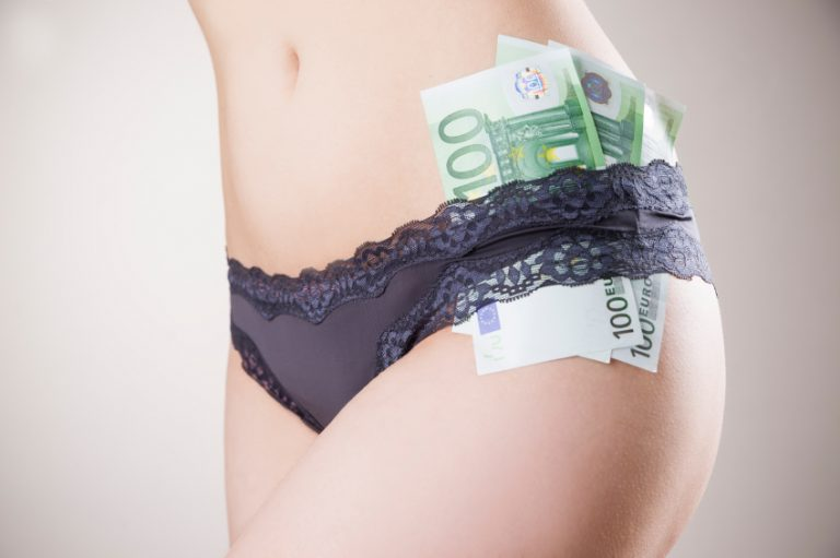 A woman with money in her lingerie, suggesting someone is buying sex from her