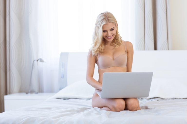 Portrait of a happy girl in lingerie using laptop computer on the bed at home
