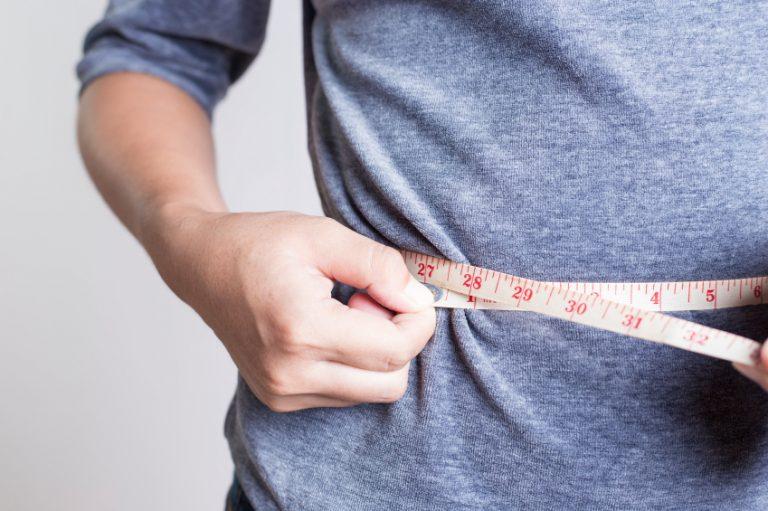 Person measuring waistline