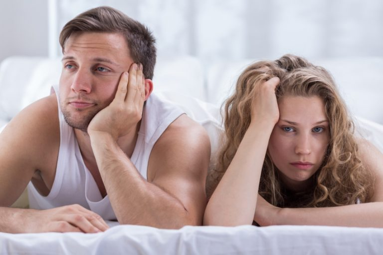 A man and woman lying in bed feeling disappointed with the vanilla sex they are having