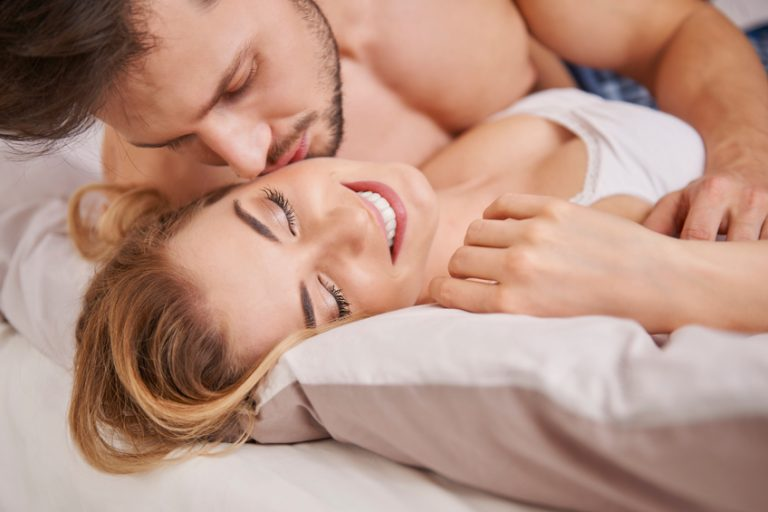 Man on top of woman in bed kissing her neck