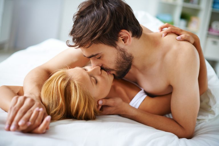 Man on top of woman in bed kissing her