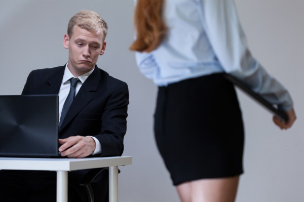 Man in suit sat at desk looks as passing woman's bottom