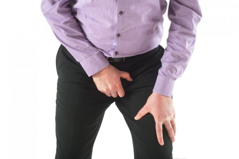 Man hold genitals over trousers