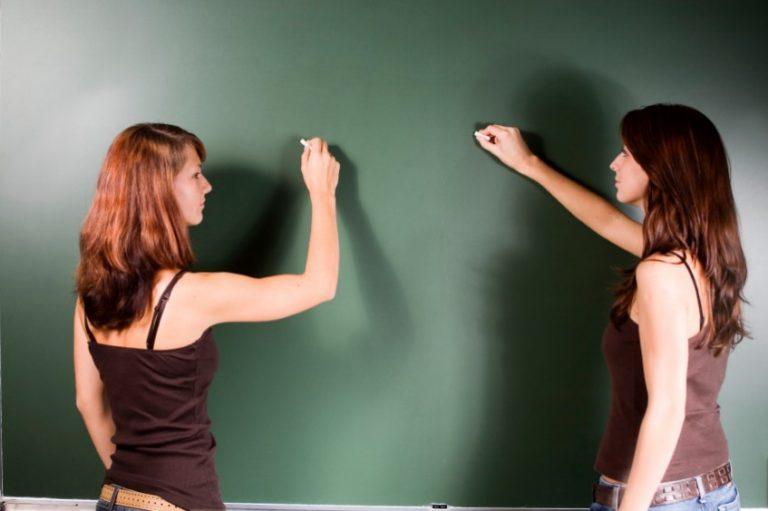 Two young teachers write on a green blackboard