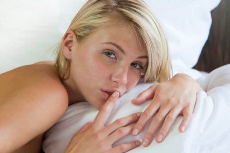 Woman lies on bed with finger over her lips